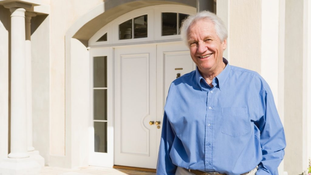 Senior man standing outside house he may have purchased with a reverse mortgage image
